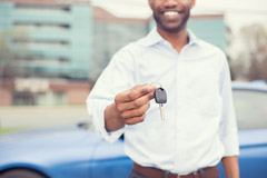 Smiling man holding car keys offering new blue car