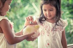 Little girl putting coin into Piggy Bank